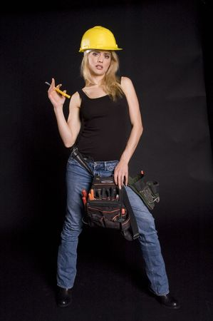 sexy blond female construction worker with hard hat and tool pouch on black background