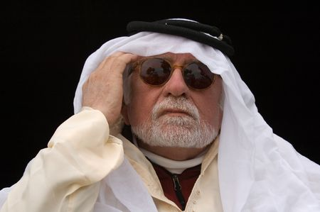 headress: older middle-eastern man with white beard, in Arabian headress and sunglasses isolated on black