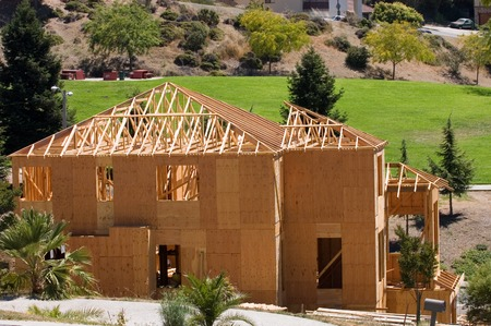 rafter: A large modern wood framed house under construction with carpenters completing the roof rafter framing