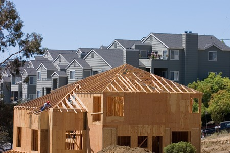 roof framing: A large modern wood framed house under construction with carpenters completing the roof rafter framing