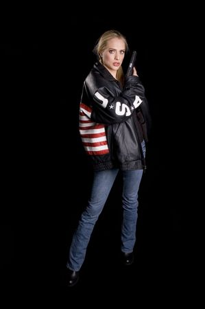 finger on trigger: Woman in a leather jacket with USA flag on back, USA on arms and a gun in her hand