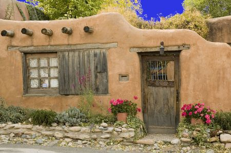 Adobe cottage with interesting door, window and flowers in front