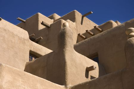 adobe pueblo: Adobe hotel facade resembling the Taos Pueblo in Santa Fe, New Mexico