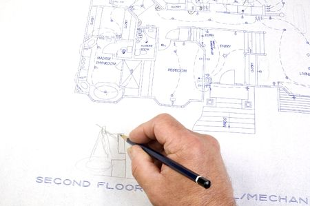 Contractor making changes to a set of building plans for a custom house with draughting tools photo