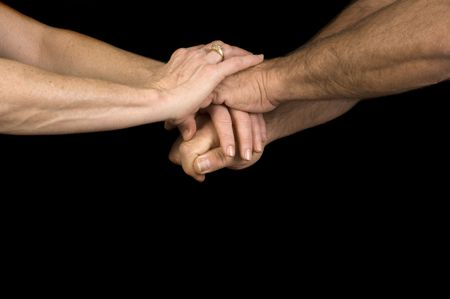 clasping: Man and woman clasping hands isolated over a black background