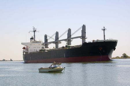 A large container ship on the Sacramento Delta in California passing a small fishing boat  Stock Photo