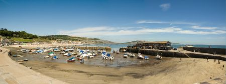 boats stranded at moorings in Lyme regis Harbor at low tide photo