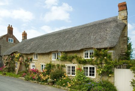 Row of pretty English traditional thatched country cottages in the small village of Abbotsbury in Dorset. Stock Photo