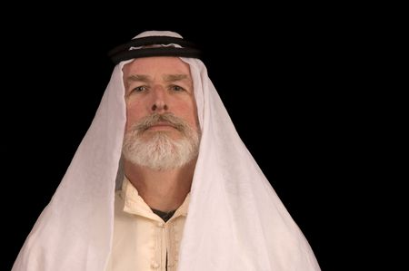older middle-eastern man with white beard, in Arabian headress isolated on black Banque d'images
