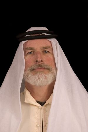 headress: older middle-eastern man with white beard, in Arabian headress isolated on black Stock Photo