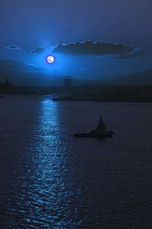 Moonrise over Athens Harbor with tug boat manouvering into position photo
