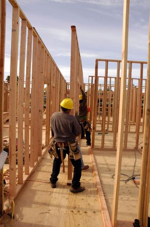 subflooring: Hispanic carpenters setting a wall at a House under construction