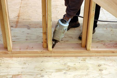 subflooring: A large modern wood framed house under construction with a hispanic carpenter nailing the bottom plate to the sub flooring