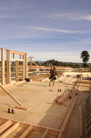 subflooring: Hispanic carpenter carrying a door header at a House under construction Stock Photo