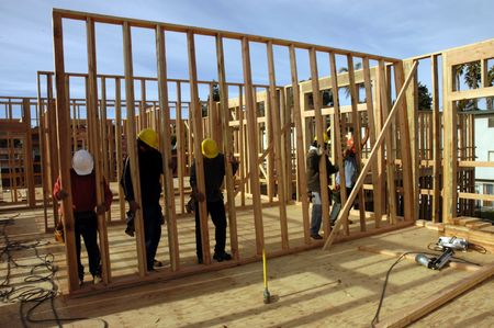 rafters: A large modern wood framed apartment building under construction with Hispanic carpenters raining a wall.