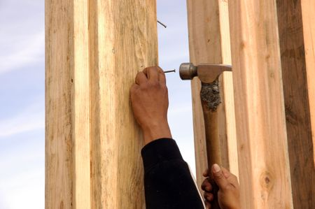 pounding: Hispanic carpenter pounding a nail in with a framing hammer at a house under construction Stock Photo