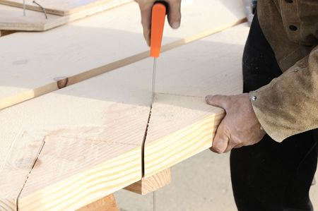 sawhorse: Carpenter finishing cut on steps for a stringer for the staricase in a commercial building