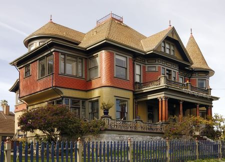 dormer: A large Victorian home with a lot of filigree and gingerbread on the facade
