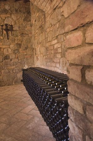 Wine bottles stacked aging along a wall in the winery