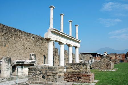 Columns that once supported a temple in Pompeii with mount Vesuvius in the distance