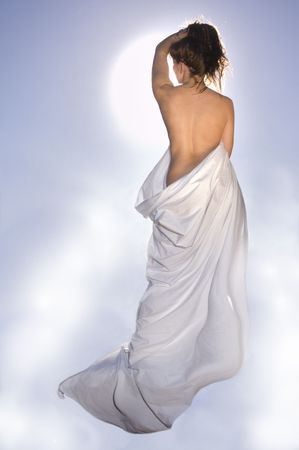 Attractive model lounging in birthday suit, wrapped in a sheet