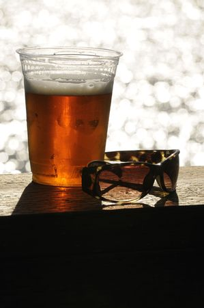 barley head: Glass of beer and a pair of sunglassas sitting on a deck handrail overlooking the ocean