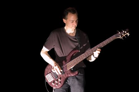 fingering: Bass Guitarist playing while isolated on black during live concert