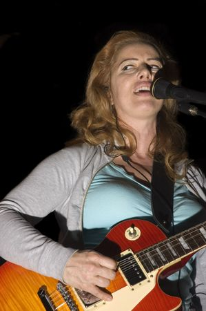 fingering: female singerGuitarist playing while isolated on black during live concert
