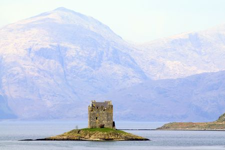 stalker castle on an island in the loch photo