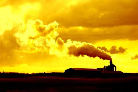 contributing: smoke rising from factory generating an environmental hazard contributing to global warming