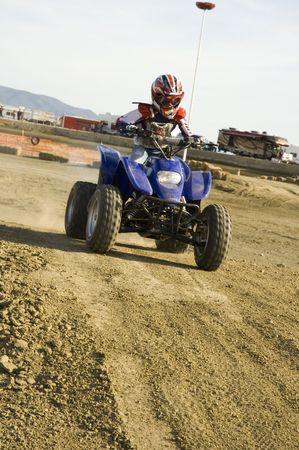 neccessary: young ATV racer on dirt track Stock Photo