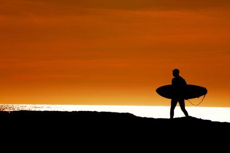 surfboard fin: Surfer walking the cliffs to the ocean at Santa Cruz, California for a final sunset ride Stock Photo