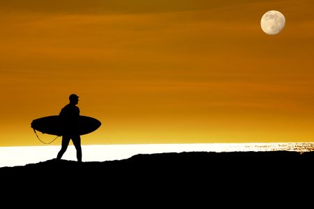 Surfer walking as the moon rises and the sun sets towards the pacific ocean along the cliffs in Santa Cruz to get that last ride photo