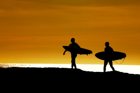 Pair of surfers heading along the cliffs at Santa Cruz for the last ride of the day as the sun sets Stock Photo