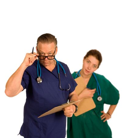 forground: Doctor in forground having just checked chart id questioning with intern standing behind slightly out of focus, both with steoscopes around neck