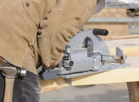 sawhorse: Carpenter cutting steps into a 4x12 stringer for a commercial building