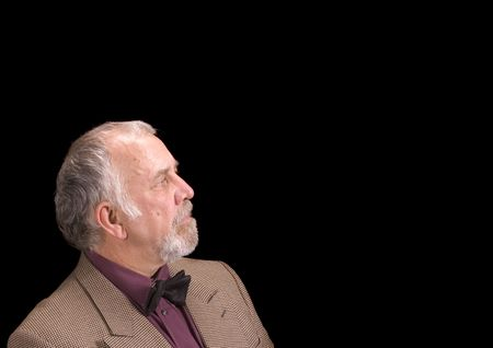 older bearded businessman looking off to his left into copy space, on his left, isolated over black photo