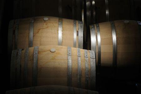 casks: Wine barrels in a dark cavern while wine ferments Stock Photo