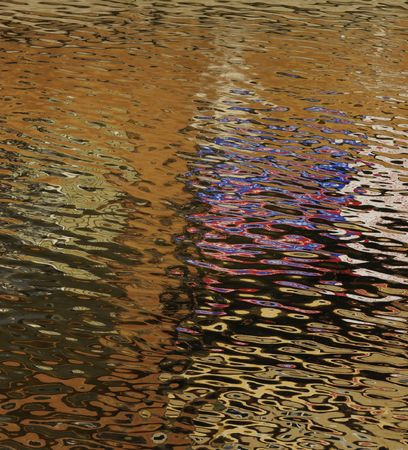 Golden reflections of the sun on ripples in a tidal area creating an abstract