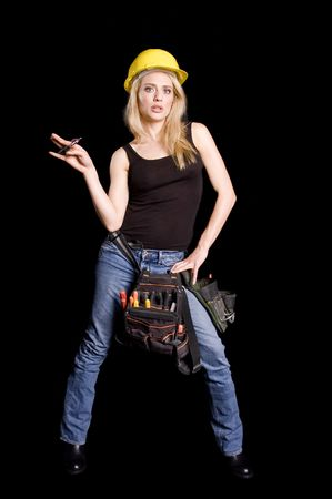 sexy blond female construction worker with hard hat and tool pouch on black background photo