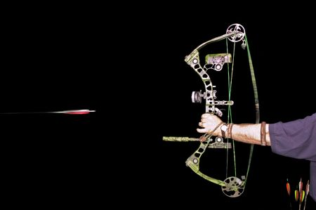 Archer shooting arrow over a black background photo