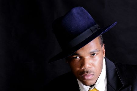 moody image of a young African American man in a hat and suit over a black background Stock Photo - 3527913