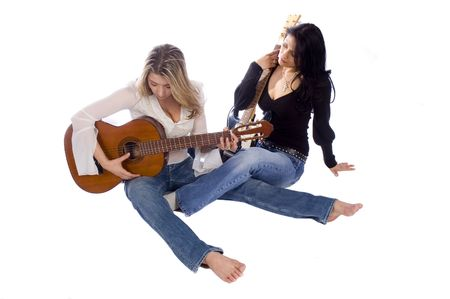 two female guitarists practicing while sitting on the floor on a white background photo