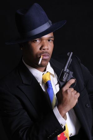 hoodlum: Male model, Kabari Jackson dressed  a gangster in a shirt, tie, jaclet and fedora.