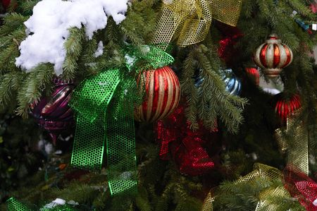 which: variety of Christmas tree ornaments on a Christmas tree which is outdoors with snow on it also adorned with lights Stock Photo