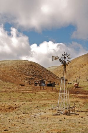 wind down: Wind driven pump on old run down farm in Central California