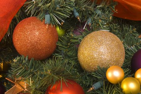 adorned: variety of Christmas tree ornaments on an artificial tree also adorned with lights Stock Photo