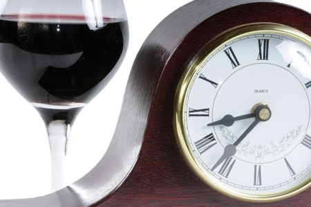 Glass of wine and mantle clock isolated