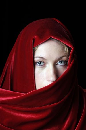 Beautiful young blond with a red velvet shawl over head photo