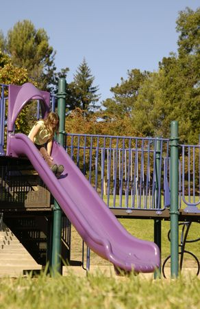 Young girl sliding down slide in playground